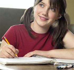Teen girl writing in notebook